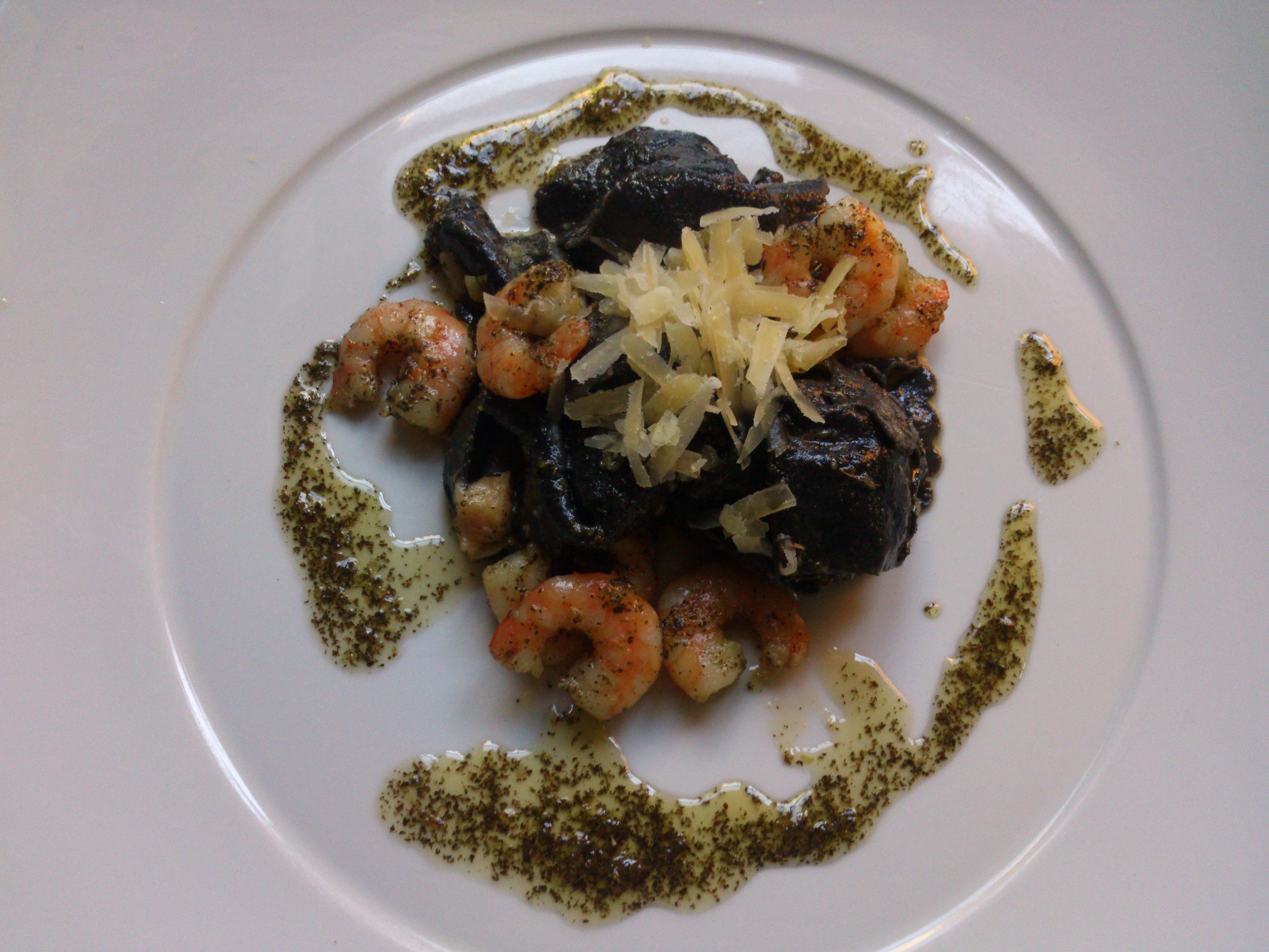 Tortellini de tinta de sepia rellenos de salmón ,con salsa pesto y gambas