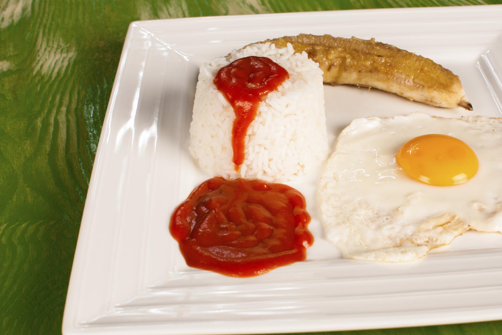 Arroz blanco con salsa de tomate, huevo y plátano frito.
