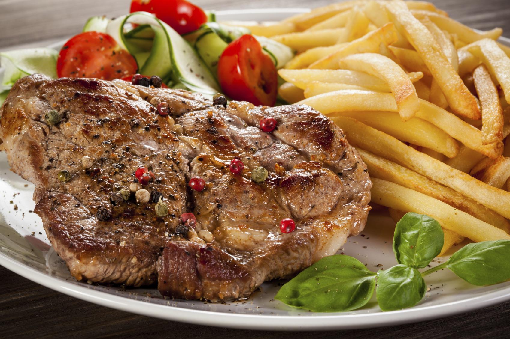 Bistec de lomo de cerdo con verduras y patatas fritas