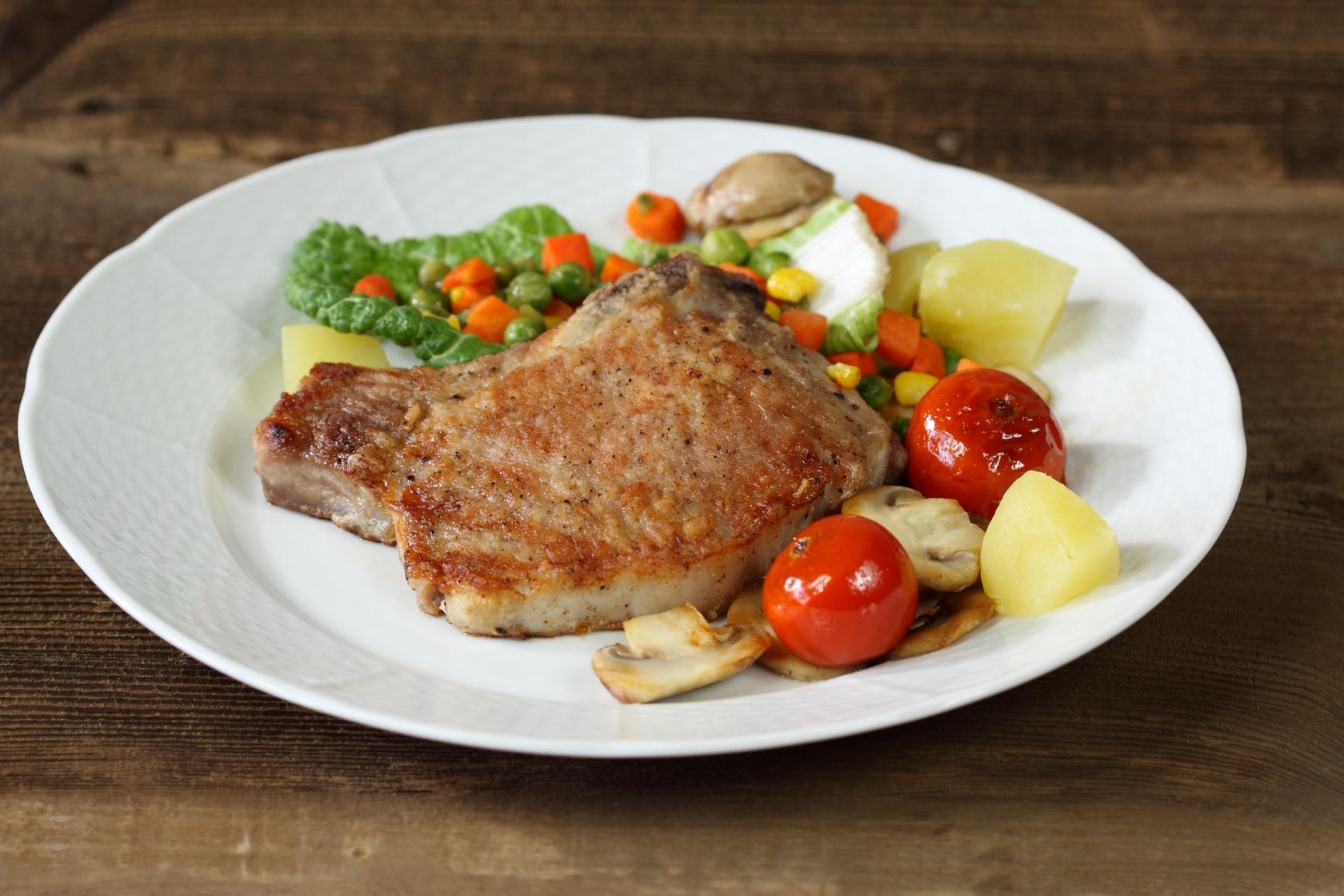 Chuletitas de cerdo sobre colchón de verduras