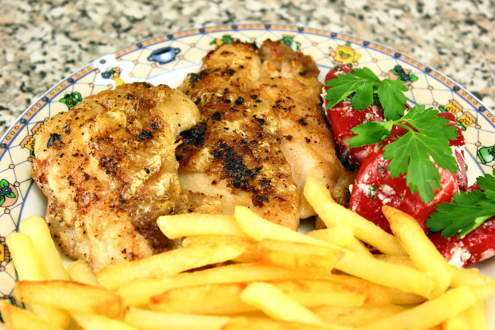 Pollo con patatas fritas y pimientos rojos