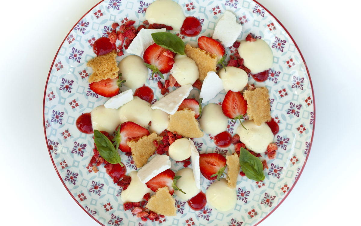 Postre de fresitas, galleta, merengue, frutos deshidratados y crema