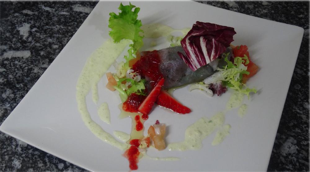 Rulo de carpaccio de langostinos relleno de ensalada con toques primaverales y cítricos.
